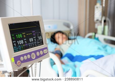 Vital Sign Monitor With Background Of Blurry Asian Woman Patient