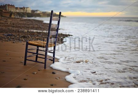 Black Wooden Armless Chair Near Sea At Daytime