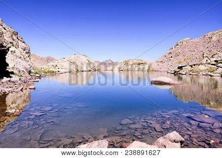 Landscape Photo Of Body Of Water Near The Mountain During Daytime. Montagnette Lake.