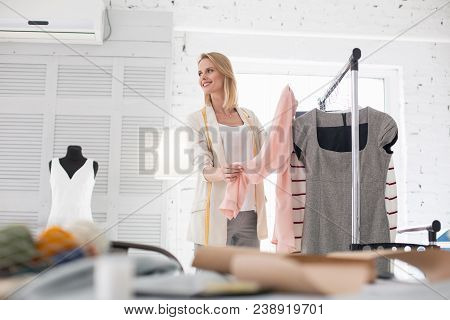 Great Choice. Merry Female Couturier Standing While Carrying Garment
