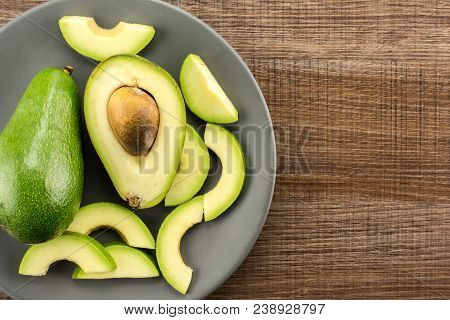 Green Smooth Avocado Sliced Composition On A Grey Plate Table Top Isolated On Brown Wood Background