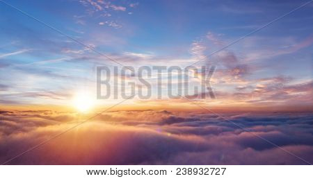 Beautiful sunset sky above clouds with dramatic light. Cabin view from airplane