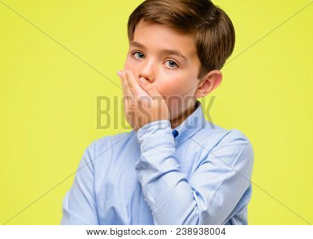 Handsome toddler child with green eyes scared in shock, expressing panic and fear over yellow background
