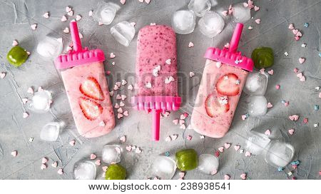 Summer Heat: Refreshing Pink Fruit Ice Cream Ith Strawberry Pieces Surrounded By Transparent And Gre