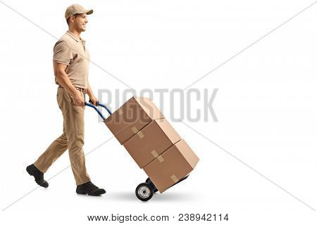 Full length profile shot of a delivery guy pushing a hand truck with boxes isolated on white background