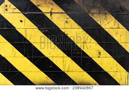 Texture Of Black And Yellow Stripes On The Wall. Hazard Or Danger Grungy Background.