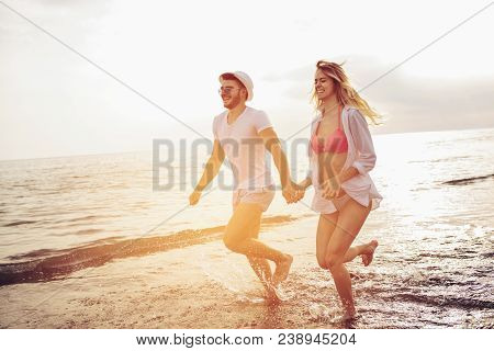 Romantic Couple Having Fun On The Beach. Happy Couple Running On Beach At Sunset.