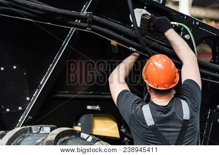 Worker Assembles Tractor Or Combine Harvester At Large Machinery Plant. Industrial Concept Of Heavy
