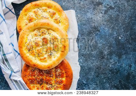 Turkish ramazan pidesi - Traditional Turkish ramadan flatbreads usually baked during ramadan month. Blue stone background. Top view. poster
