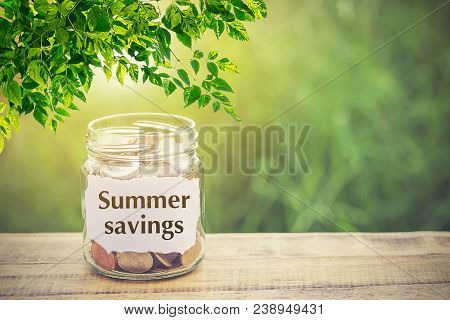 Money In The Jar On Wooden Table And Text Summer Savings With Filter Effect Retro Vintage Style. The