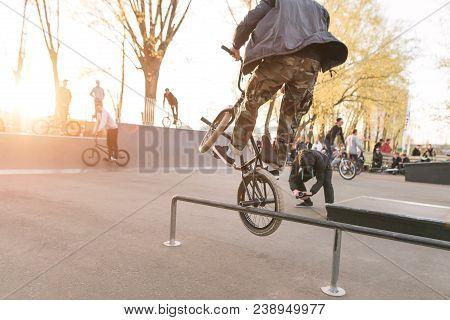 The Crazy Bmx Rider Performs Tricks In The Skate Park On The Background Of The Sunset. Bike Leap Bmx