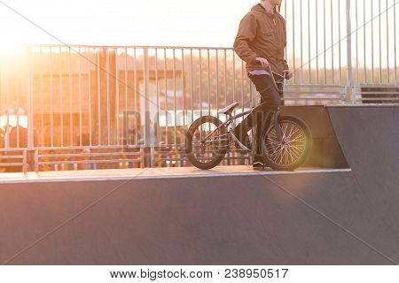 Bmx Cyclist Is Standing On A Ramp Skate Park On The Background Of The Sunset. Bmx Bicycle And Cyclis
