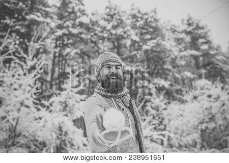 Hipster In Thermal Jacket, Hat, Scarf, Beard Warm In Winter. Bearded Man Smile With Snowball In Snow