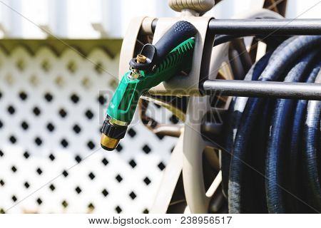 Watering Garden Equipment, Garden Hose Storage And Pistol Nozzle. Garden Hose Pistol On Background O