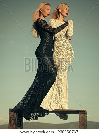 Fashion And Beauty. Women Wearing Black And White Dresses. Two Girls With Long Blond Hair Posing On