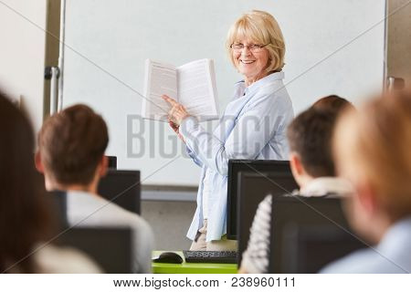 Woman as lecturer explains textbook in university seminar
