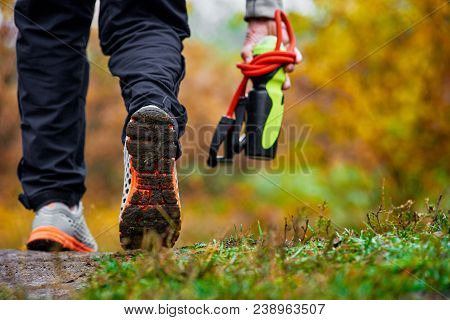 Closeup Of Man With Bottle And Expander Walking In Autumn Forest