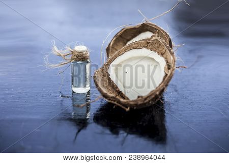 Close Up Of Raw Organic Coconut Or Cocos Nucifera With Its Essence In A Transparent Bottle Used In M
