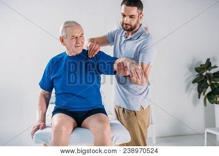 Portrait Rehabilitation Therapist Doing Massage To Senior Man On Massage Table