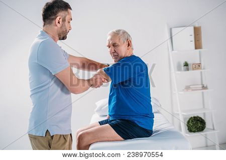 Side View Of Physiotherapist Doing Massage To Senior Man On Massage Table