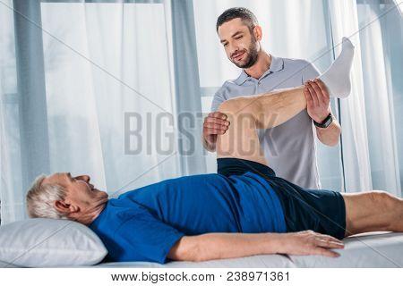Side View Of Rehabilitation Therapist Massaging Senior Mans Leg On Massage Table