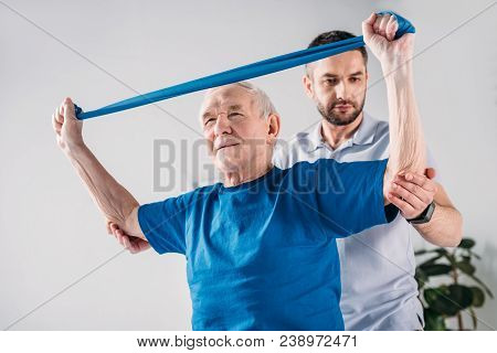 Focused Rehabilitation Therapist Assisting Senior Man Exercising With Rubber Tape