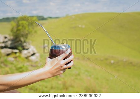 Hand Of Woman Holding Traditional Mate, Mate, With Green Field View. (chimarrao)