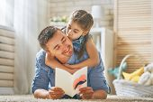 Happy father's day! Child daughter congratulating dad and giving him postcard. Daddy and girl smiling and hugging. Family holiday and togetherness. poster