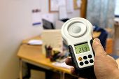Measuring office lighting with lux meter. Lighting ergonomics on workstation. poster