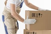 relocation services concept. Mover's hands In uniform carrying cardboard Box. Loader puts cardboard boxes isolated on white background. Worker mover unloading paper box. Delivery man. poster