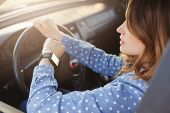 Busy young woman drives car and looks at watch, stuck in traffic jam, hurries to work, being nervous and stressed, feels impatient, keeps hands on wheel. Transportation, vehicle and time concept poster