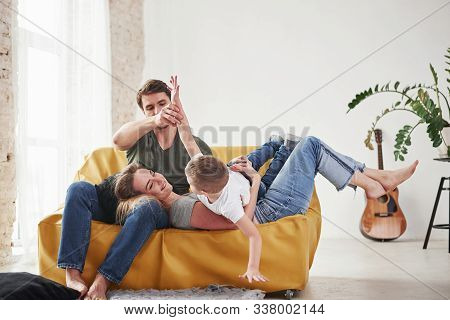 Kid Lying On His Parents. Happy Family Have Fun On The Yellow Sofa In The Living Room Of Their New H