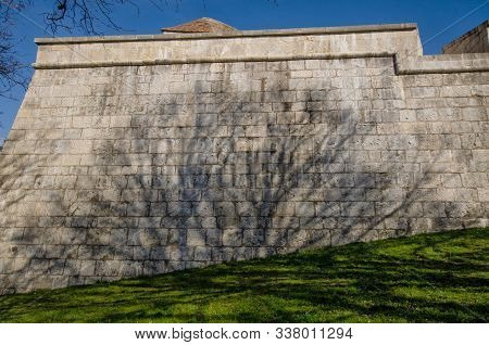 Fragment Of An Old Fortified Wall Of Stone Blocks. There Is A Shadow From A Tree Without Leaves And
