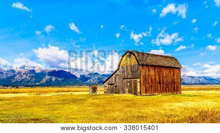 An Abandoned Barn At Mormon Row With In The Background Cloud Covered Peaks Of The Grand Tetons In Gr