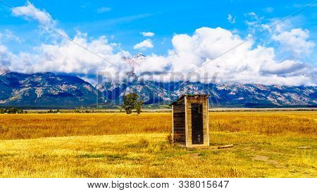 An Outhouse At Mormon Row With In The Background Cloud Covered Peaks Of The Grand Tetons In Grand Te