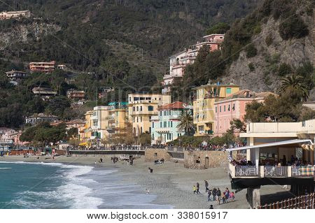 Monterosso, Italy - April 2 2018: The View Of Shoreline, People Walking On The Beach And Colorful Ho