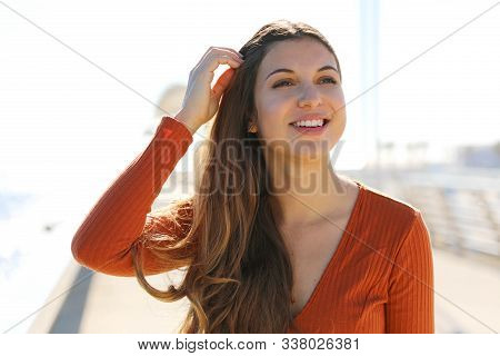 Happy Young Carefree Woman Relaxed On The Beach. Close Up Portrait Of Beautiful Girl With Wind Flutt