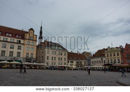 Tourists Crowd The Sidewalk Cafes And Shops In The Medieval Tallinn Town Square In The Walled City O