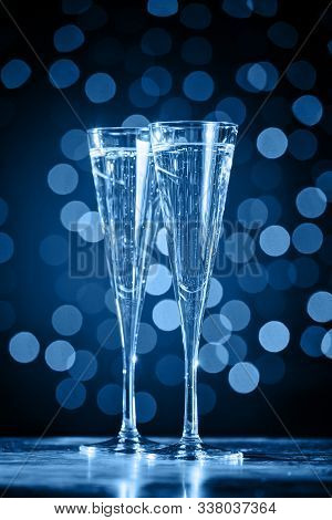 Two Glasses Of Champagne On Classic Blue Bokeh Background. Holiday Concept. Festive Bokeh Background