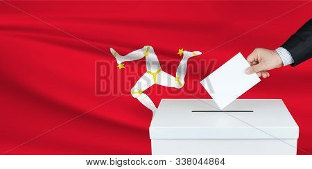 Election In Isle Of The Man. The Hand Of Man Putting His Vote In The Ballot Box. Waved Isle Of The M