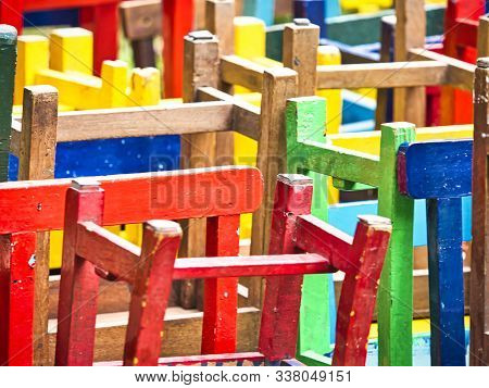 Stack Of Assorted Colorful Wooden Chairs In Random Disarray, For Children At School