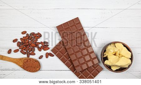 Bars Of Milk Chocolate, Cocoa Butter, Cocoa Powder And Cocoa Beans On Light Wooden Background. Top V