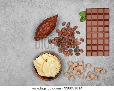 Bar Of Milk Chocolate, Cocoa Butter, Cocoa Pod, Cane Sugar Cubes, Mint And Cocoa Beans On Gray Stone