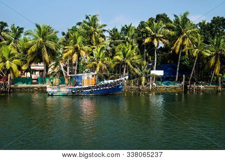 Ocean Fishing Boat Along The Canal Kerala Backwaters Shore With Palm Trees At A Sunny Day Between Al