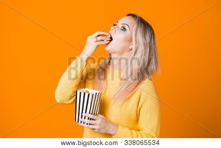 Young Cheerful Woman Watching A Blockbuster And Eating Popcorn. Fan Movie Concept On Yellow Backgrou