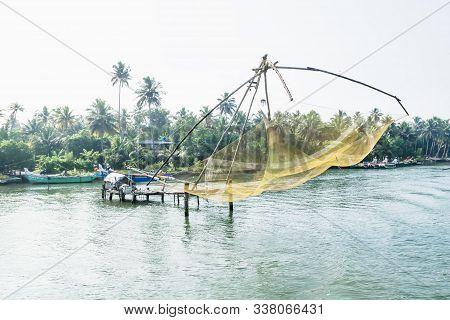 Yeollow Chinese Fisher Net Along The Kollam Kottapuram Waterway Along Palm Tree River Shore, Kerala,