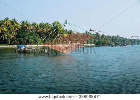 Orange Chinese Fisher Net Along The Kollam Kottapuram Waterway Along Palm Tree River Shore, Kerala,