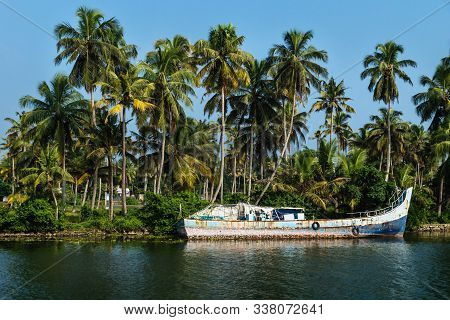 Abandoned Ocean Fishing Boat Along The Canal Kerala Backwaters Shore With Palm Trees At A Sunny Day