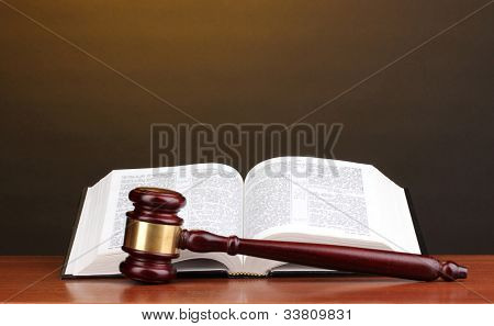 Judge's gavel and open book on wooden table on brown background