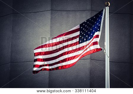 Flag Of The United States Of America, Waving On A Pole Against A Concrete Wall. Dark Processing With